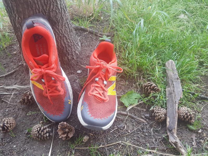 Trailrunning Schuh von New Balance steht vor einem Baum